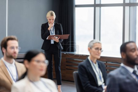 Businesswoman with smartphone and paper folder standing near interracial business people in conference room