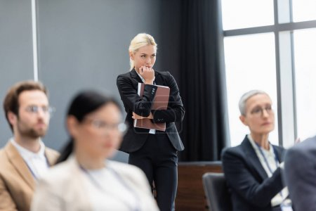 Photo for Focused businesswoman with paper folder standing near blurred colleagues in conference room - Royalty Free Image