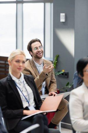 Photo pour Homme d'affaires joyeux avec ordinateur portable pointant avec la main pendant le séminaire - image libre de droit