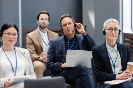 Mature businessman in headset holding laptop near interracial business people in conference room