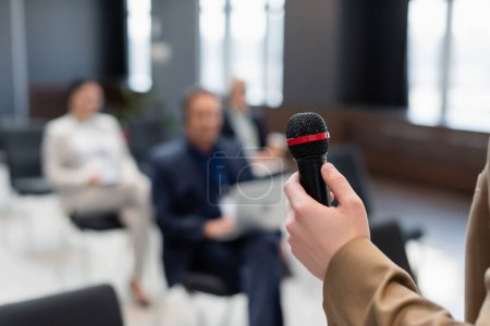 Photo for Speaker holding microphone near blurred participants during business conference - Royalty Free Image