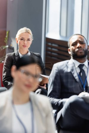 Photo for Selective focus of blonde businesswoman near interracial colleagues on blurred foreground - Royalty Free Image