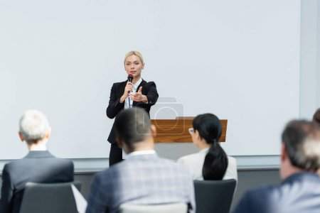 Photo for Young lecturer talking in microphone while pointing with finger at business people on blurred foreground - Royalty Free Image