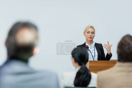 young speaker gesturing while talking to blurred business people during seminar