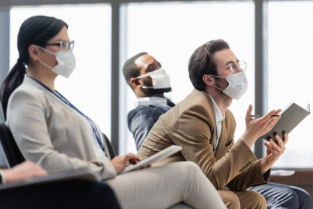 young businessman in medical mask asking question while holding notebook on seminar