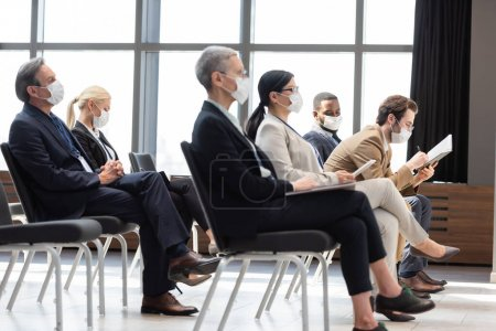Photo for Multicultural business people in medical masks sitting in conference room during seminar - Royalty Free Image