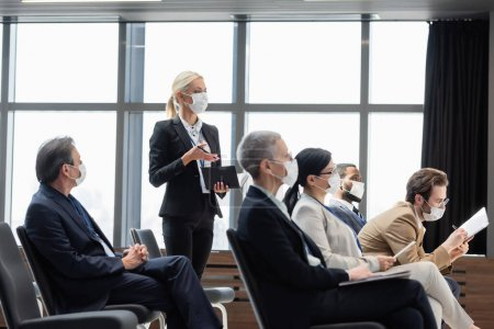 young businesswoman in medical mask holding notebook while asking question during seminar