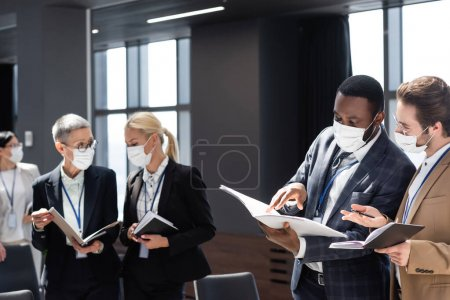 Photo for African american businessman pointing at documents during conversation with colleague - Royalty Free Image