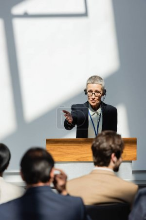 Photo for Back view of blurred business people near lecturer pointing with hand during conference - Royalty Free Image