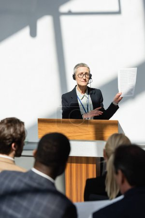 Photo for Middle aged speaker pointing at document near blurred audience during business conference - Royalty Free Image
