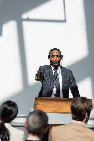 Photo pour Conférencier afro-américain pointant vers le public sur le premier plan flou pendant le séminaire - image libre de droit