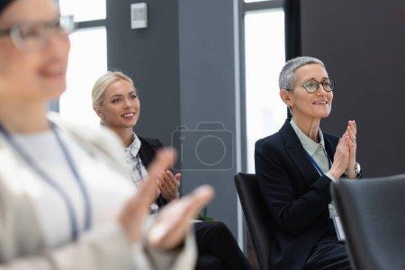 Photo pour Heureux interracial femmes d'affaires applaudissant lors de la conférence, flou premier plan - image libre de droit