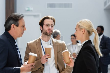 successful businesspeople holding paper cups during conversation on coffee break