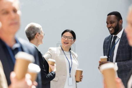 Photo for Selective focus of happy interracial business colleagues talking during conference - Royalty Free Image