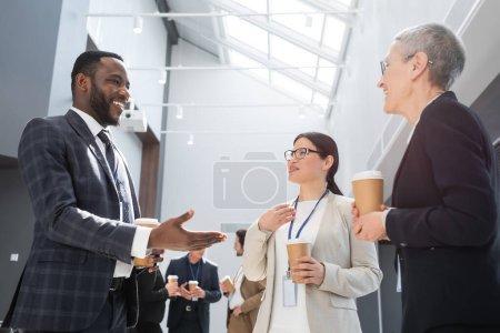 Photo pour Heureux homme d'affaires afro-américain pointant avec la main près des femmes d'affaires interracial - image libre de droit