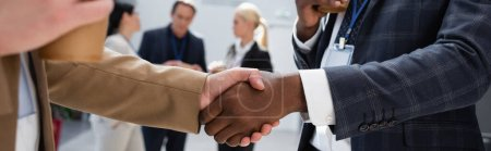 Photo for Interracial businessmen shaking hands near colleagues on blurred background, banner - Royalty Free Image