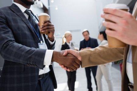 Photo pour Hommes d'affaires interracial serrant la main près de collègues sur fond flou - image libre de droit