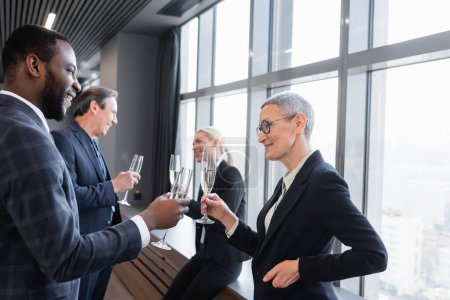 interracial businesspeople clinking champagne glasses during break in conference