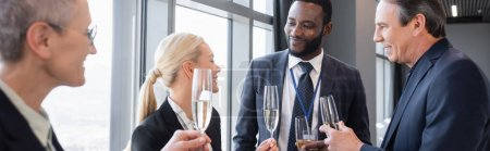 multiethnic businesspeople holding champagne glasses during discussion on conference, banner
