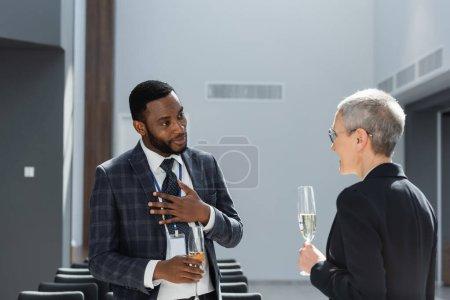 Photo pour Homme d'affaires afro-américain tenant la main sur la poitrine lors d'une conversation avec un collègue d'âge moyen - image libre de droit