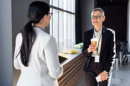 Photo for Middle aged businesswoman holding takeaway drink and cellphone during conversation with blurred colleague - Royalty Free Image