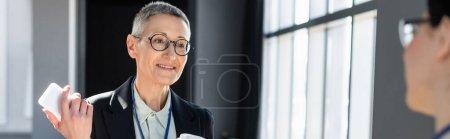 Photo pour Femme d'affaires mature avec smartphone parlant à un collègue flou pendant la conférence, bannière - image libre de droit