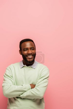 Smiling african american man with crossed arms looking at camera isolated on pink