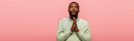 Photo pour Africain américain avec des mains priantes levant les yeux isolés sur rose, bannière - image libre de droit