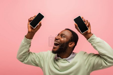Photo for Happy african american man looking at smartphone with blank screen isolated on pink - Royalty Free Image