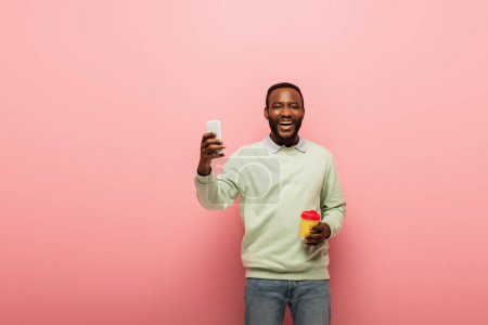 Photo for Positive african american man holding cellphone and coffee to go on pink background - Royalty Free Image