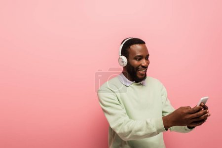 Lächelnder afrikanisch-amerikanischer Mann mit Kopfhörer und Smartphone auf rosa Hintergrund