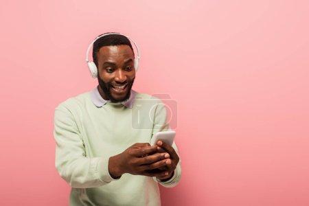 Afroamerikaner mit Kopfhörer, Handy und Lächeln auf rosa Hintergrund