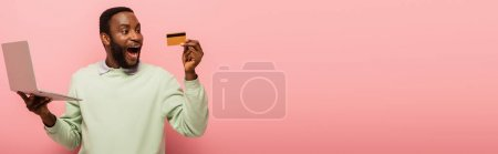 Photo for Astonished african american man looking at credit card while holding laptop on pink background, banner - Royalty Free Image