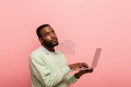 Foto de Hombre afroamericano reflexivo mirando hacia otro lado mientras se utiliza el ordenador portátil aislado en rosa - Imagen libre de derechos