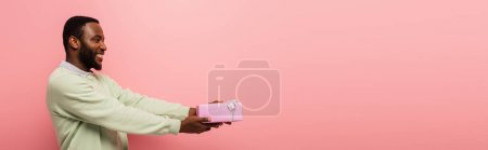 smiling african american man holding gift box in outstretched hands isolated on pink, banner
