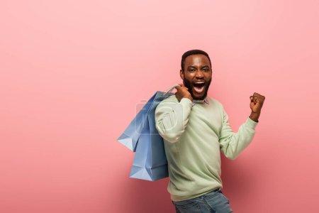 Photo pour Homme afro-américain ravi avec des sacs à provisions montrant geste de joie sur fond rose - image libre de droit