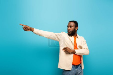 young african american man pointing aside with finger on blue background