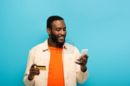 Photo for Smiling african american man holding credit card while using cellphone isolated on blue - Royalty Free Image