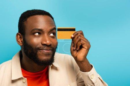 Photo pour Heureux et rêveur homme afro-américain détournant les yeux tout en tenant la carte de crédit isolé sur bleu - image libre de droit