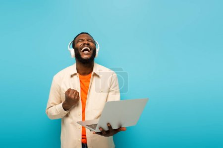 Photo for Excited african american man in headphones showing success gesture while standing with laptop isolated on blue - Royalty Free Image