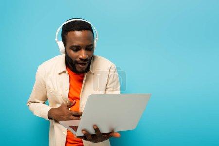erstaunt afrikanisch-amerikanischer Mann mit Kopfhörer schaut auf Laptop isoliert auf blau