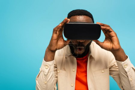 Photo for Shocked african american man touching vr headset while gaming isolated on blue - Royalty Free Image