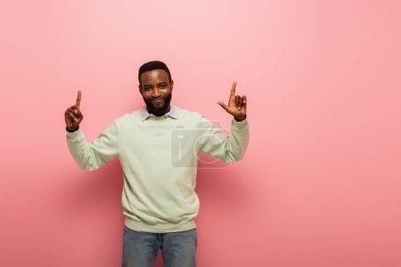 Photo pour Joyeux homme afro-américain souriant à la caméra et pointant vers le haut avec les doigts sur fond rose - image libre de droit