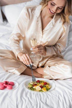 Mujer sonriente con champán sentada cerca de macarrones y ensalada de frutas en la cama