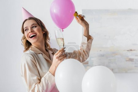 Smiling woman with party horn and champagne celebrating birthday near balloons at home
