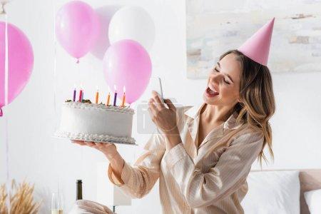 Fröhliche Frau mit Geburtstagstorte fotografiert auf Smartphone bei Party zu Hause