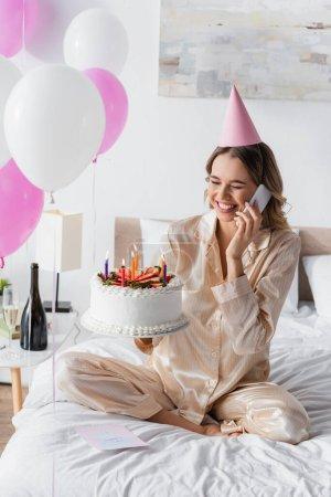 Mujer alegre hablando en el teléfono móvil y celebración de pastel de cumpleaños durante la celebración en el dormitorio