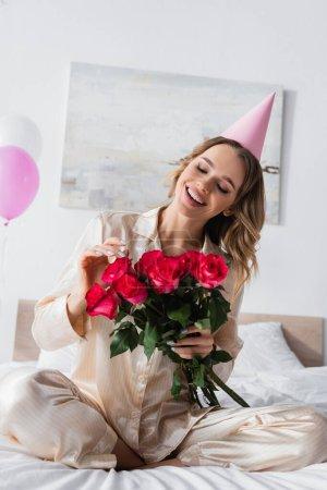 Photo pour Jeune femme en pyjama et bonnet de fête tenant des roses sur le lit - image libre de droit