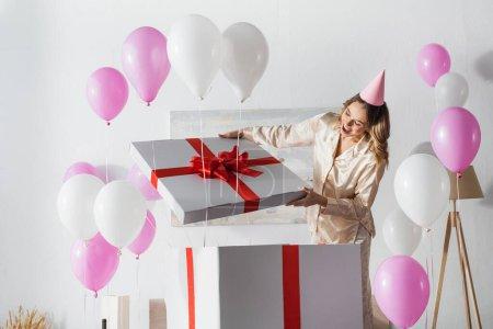 Photo pour Femme étonnée ouvrant une grande boîte cadeau pendant la fête d'anniversaire à la maison - image libre de droit