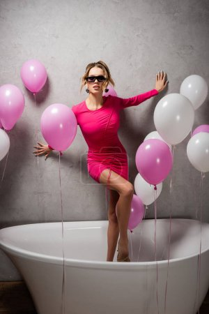 Photo for Fashionable woman standing in bath near balloons - Royalty Free Image
